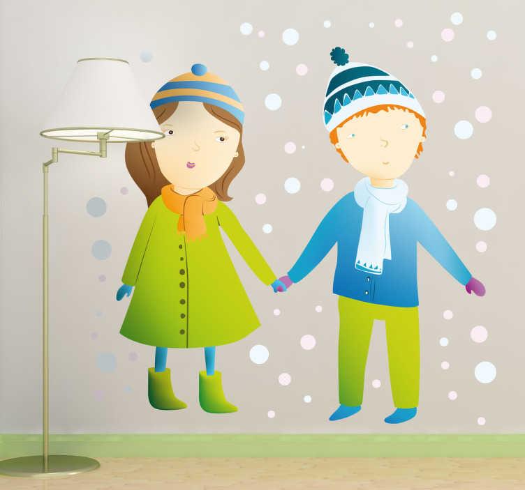 TenStickers. Naklejka dzieci na śniegu. Kolorowa naklejka na ścianę przedstawiająca chłopca i dziewczynkę w zimowych strojach, którzy stoją na śniegu.