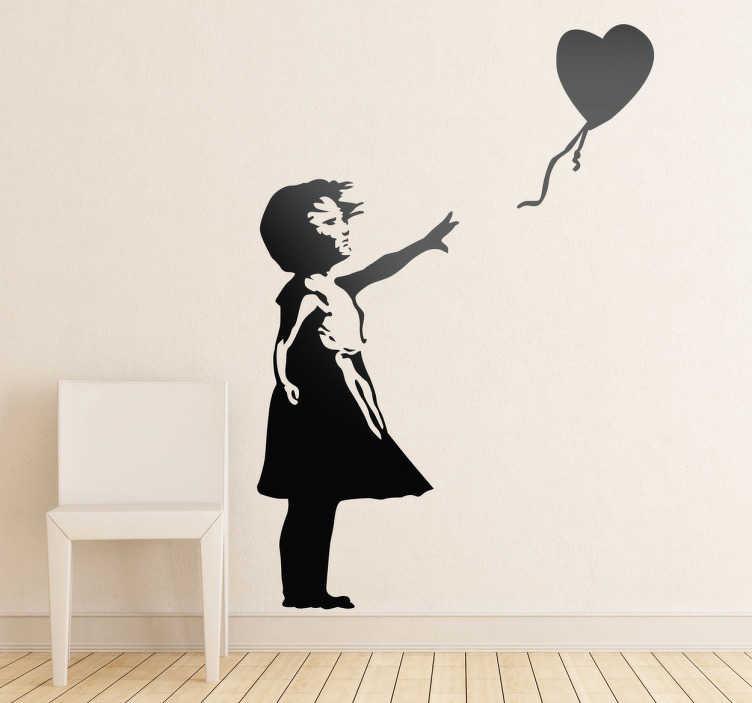 TenStickers. Autocolante decorativo rapariga e balão Banksy. Autocolante decorativo inspirado na arte Banksy, ilustrando a silhueta de uma rapariga a soltar um balão em forma de coração.