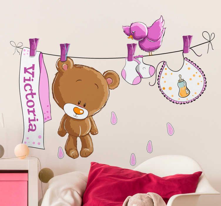 TenStickers. Sticker enfant ours en peluche sur séchoir rose. Stickers décoratif tout plein de tendresse de ce petit ours en peluche tout propre sur une corde à linge au milieu des autres affaires de bébé.
