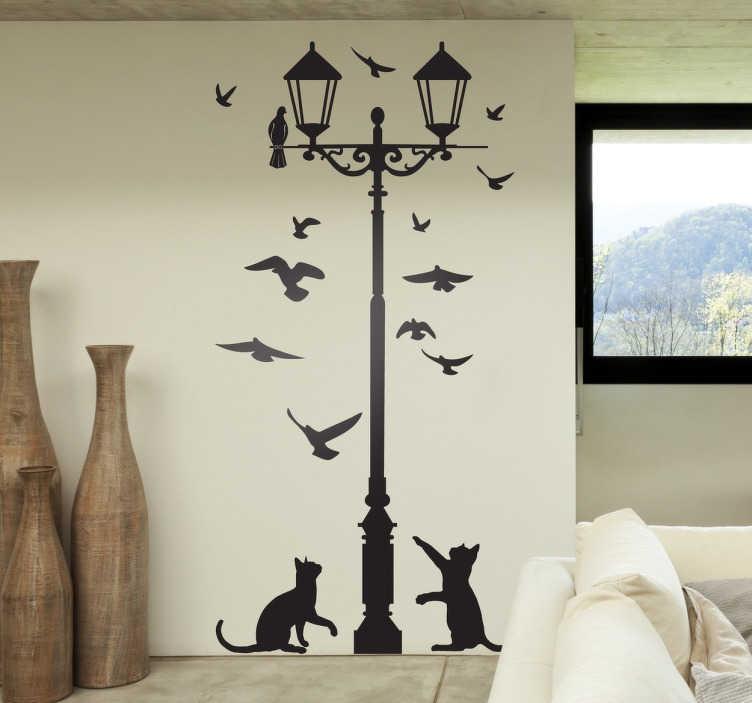 TenStickers. Muursticker lantaarnpaal duiven en katten. Deze muursticker is een decoratief en leuk ontwerp van een lantaarnpaal met twee katten en meerdere duiven die de lucht in vliegen.