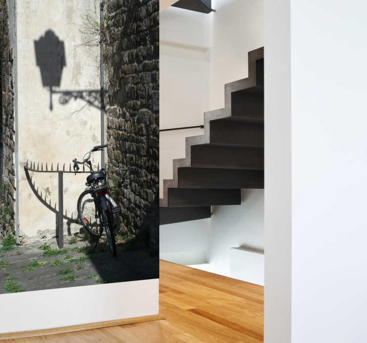 TenStickers. Sticker decorativo ombra di lampione. Fotomurale raffigurante lo scorcio di un viottolo di paese; sono visibili una bicicletta e un'ombra di lampione proiettata sul muro.