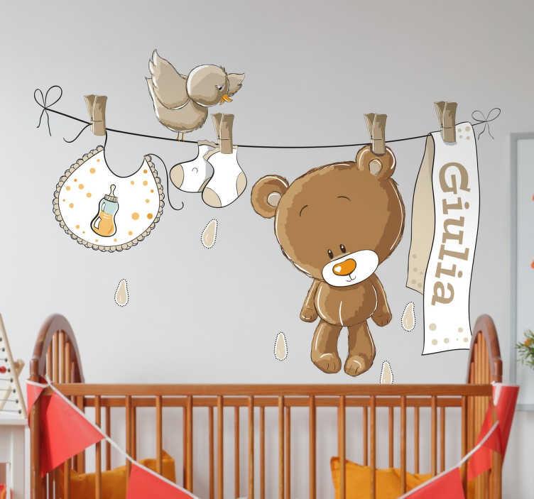 TenStickers. Sticker enfant personnalisable peluche marron. Sticker pour enfant avec prénom personnalisable, représentant une peluche marron accrochée à une corde à linge, avec un bavoir et des chaussettes.