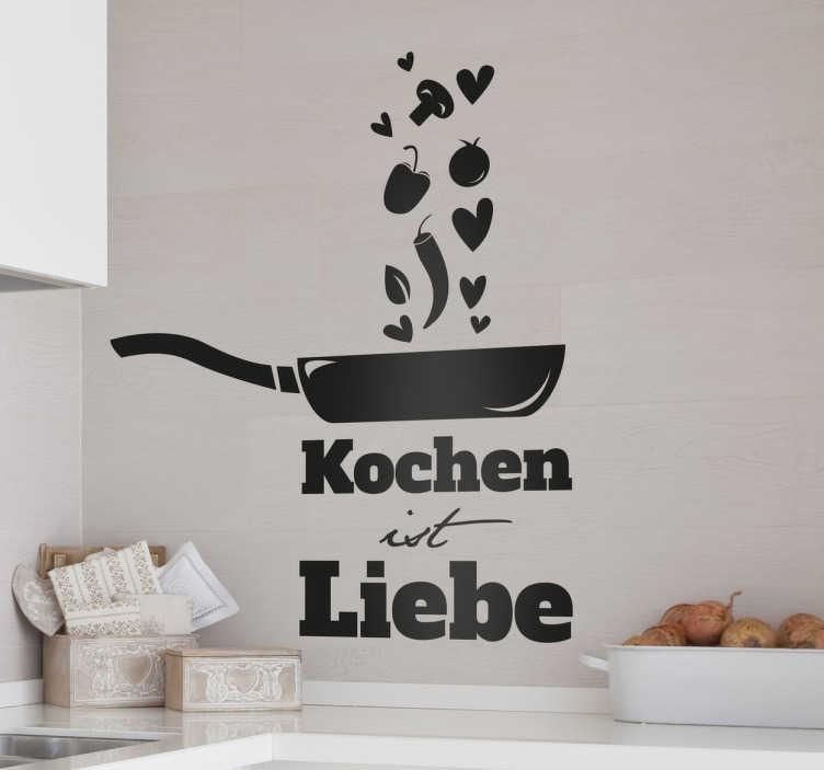 """TenStickers. Wandtattoo Kochen ist Liebe. Das Wandtattoo für die Küche umfasst die Aufschrift """"Kochen ist Liebe"""" und eine Pfanne, aus der verschiedene Gemüsesorten und Herzchen aufsteigen."""