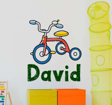 This customisable decorative wall vinyl for children featuring an illustration of a tricycle and the name of your choice underneath