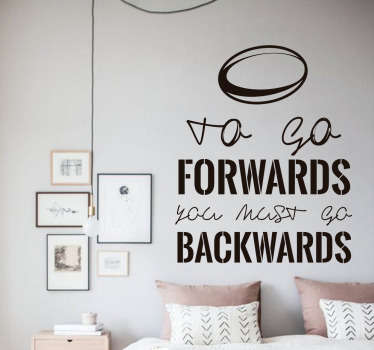 "The wall sticker consists of the message ""to go forwards you must go backwards"" with an image of a rugby ball above the text."