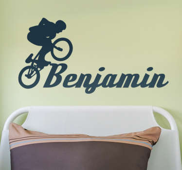 Silhouette wall decal with customizable name and the profile of a young man doing tricks with his bicycle. Anti-bubble vinyl.