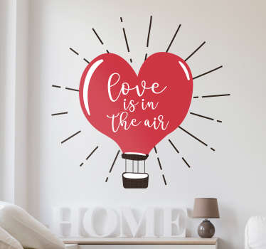 "Vinilo decorativo con el dibujo de un globo aerostático con forma de corazón en cuyo interior aparece la frase ""Love is in the air""."