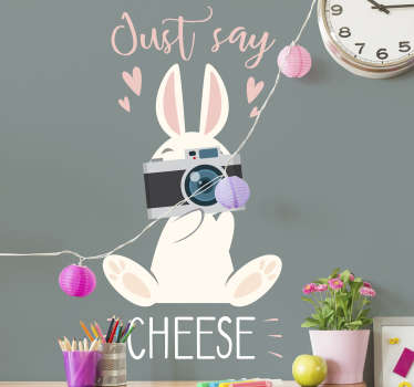 Decorate the room of the children with this cute bunny. The wall decal consists of a bunny that is holding a holding a camera and says 'Just say cheese'.