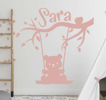 Personalisable name kids wall sticker with the design of a baby cartoon swinging on a tree. Provide the name for the design and choose the size.