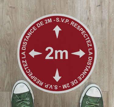 Un autocollant sol conçu sur un fond rond de couleur rouge. Dans ce sticker rond, il est inscrit avec un texte indiquant qu'il faut garder une distance de sécurité de 2 mètres.