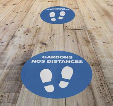 """Un autocollant sol avec le dessin des empreintes de pied avec un texte qui dit """"s'il vous plaît gardez vos distances"""". Nous l'avons dans différentes tailles."""