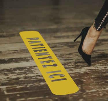 """Un sticker sol avec le texte """"patientez ici"""" sur un fond rectangulaire simple. Cet autocollant sol est facile à appliquer et la taille est au choix."""