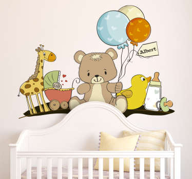 A lovely customisable nursery decal from our collection of teddy stickers illustrating a giraffe, a buggy, toys, a bottle, balloons and a teddy bear.