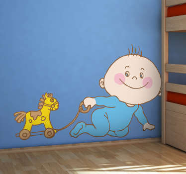 A kids wall sticker illustrating a baby boy playing with his wooden horse on the floor. Brilliant playroom decal to create a fun atmosphere.