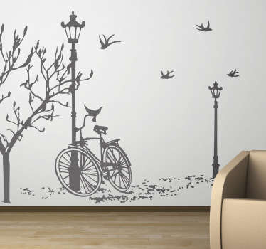 A wall sticker representing a drawing of an abanded bicycle under a lamp post and a leafless tree.
