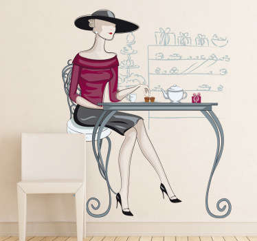 A wall sticker of an elegant women with a large hat sat at a table to have some tea.