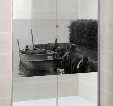 Shower Decal - A black and white still shot of a young boy sitting along side a docked wooden boat. A distinctive feature great for the bathroom