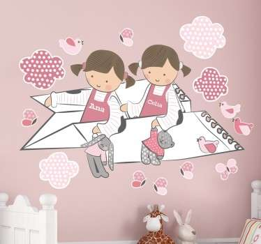 Playful pink personalised kids wall sticker showing two little girls flying past the birds and clouds on a paper aeroplane while holding their teddy bears. This polka dot wall sticker can be customised to show any name on the girls' dresses in any size you want.