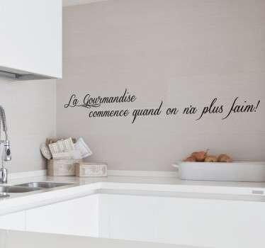 """Sticker texte """"La gourmandise commence quand on n'a plus faim"""", idéal pour décorer les murs de votre cuisine en toute simplicité."""