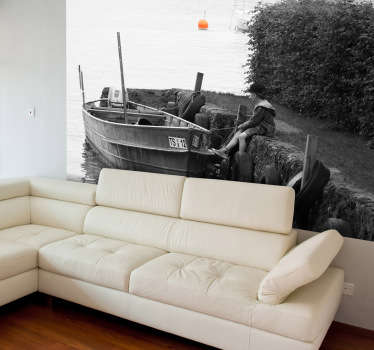 A black and white still shot of a young boy sitting along side a docked wooden boat. A photo mural from our collection of sea wall stickers.