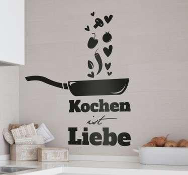 """Das Wandtattoo für die Küche umfasst die Aufschrift """"Kochen ist Liebe"""" und eine Pfanne, aus der verschiedene Gemüsesorten und Herzchen aufsteigen."""