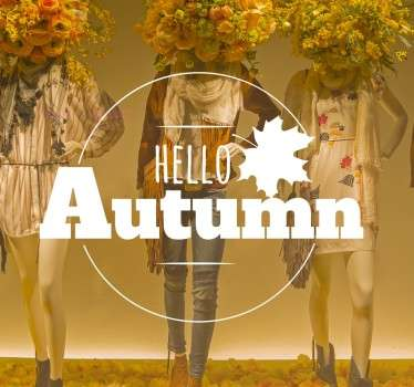 "Sticker featuring the text ""Hello Autumn"" in a decorative circle alongside the design of a falling maple leaf, this vinyl is perfect for shop windows!"