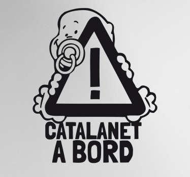 Vinilos bebé a bordo en catalán en el que aparece una divertida ilustración de un niño pequeño con chupete.