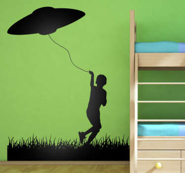 This wall sticker consists of a little boy running around in the grass, flying his kite. The kite just so happens to be a UFO.