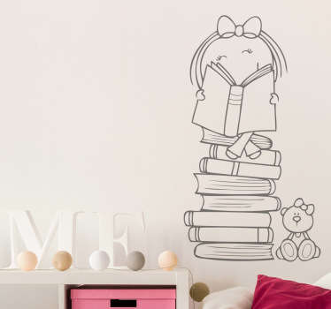 The wall sticker consists of a little girl sitting on a mountain of books and reading.