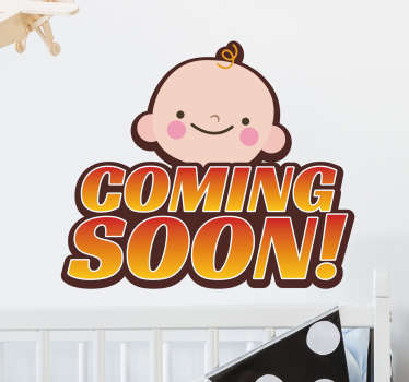 "The wall sticker consists of the phrase ""coming soon!' with a smiling baby face above."