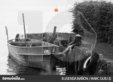 TenVinilo. Vinilo niño y barca. Fotomural de autor. Fotografía en blanco y negro de un niño en el borde de un amarre con una barca al lado. De fondo una boya en color.