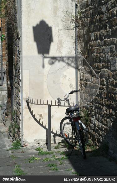 TenVinilo. Vinilo sombra farola y bicicleta. Fotomural de autor. Fotografía de una bicicleta clásica de paseo y sobre la pared del fondo se observa la sombra de una farola.