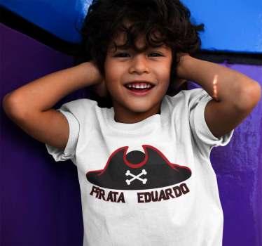 Camiseta pirata para niños y niñas con el diseño de un sombrero de colores oscuros con un ribete de color rojo y dos huesos cruzados.