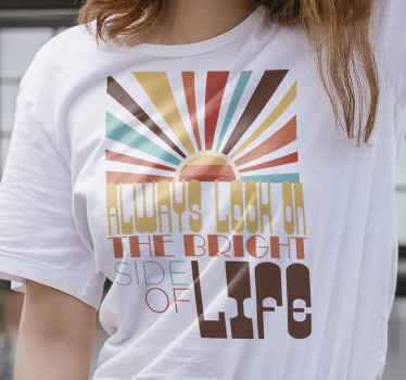 Un t-shirt de citation de motivation pour vous faire voir tout de manière positive avec un coucher de soleil plein de couleurs comme le bleu, le marron, le jaune et le rouge.