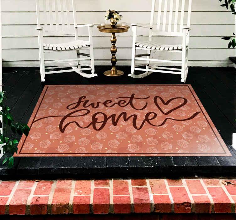 """TenStickers. Dywanik na zamówienie w muszle i gwiazdy. Fantastyczny wzór muszelek i gwiazdek w odcieniach czerwieni z napisem """"słodki dom"""". Nasze dywaniki winylowe można prać i są bardzo odporne."""
