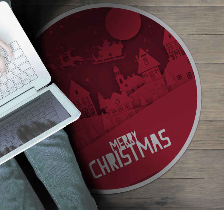 TenStickers. Christmas Scenery Vinyl rug. This Christmas vinyl rug features a picture of Santa flying through a town on his sleigh with the text 'Merry Christmas' across the bottom.