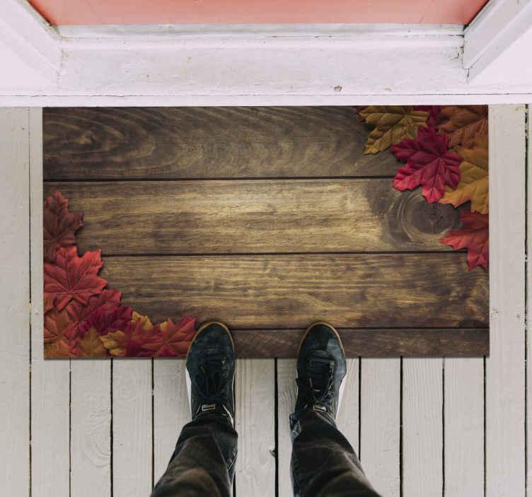 TenVinilo. Alfombra vinilo madera con hojas otoño. Alfombra vinílica entrada con tablones de madera cubiertos en las esquinas por hojas otoñales. Alta calidad ¡Envío express!