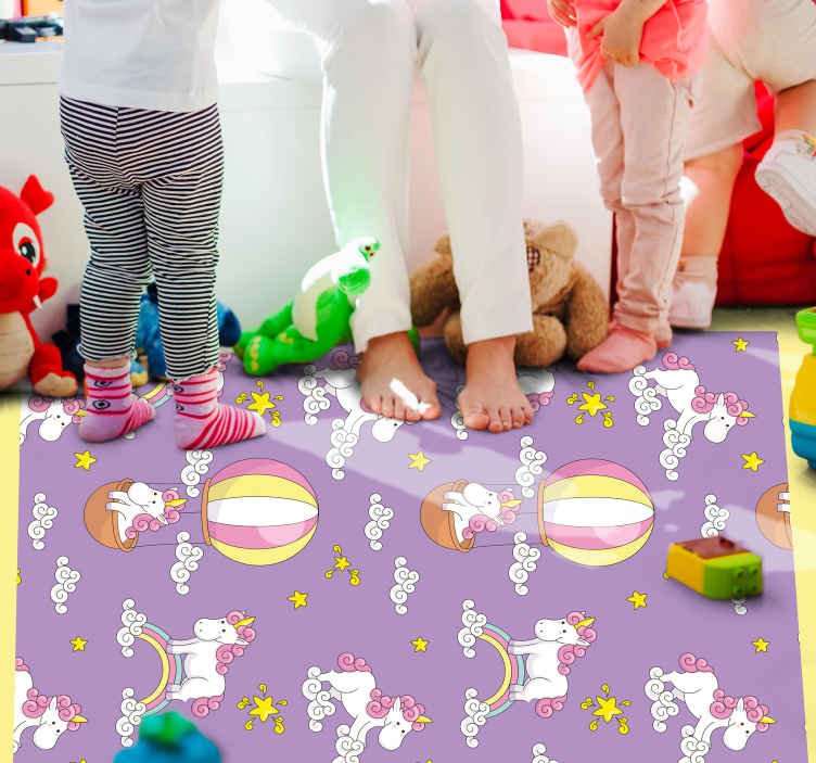 TenVinilo. Alfombra vinilo infantil unicornios en globos. Alfombra vinilo infantil con estampado de globos y unicornios morados con estrellas, arcoíris y nubes para decorar la habitación de tus hijos