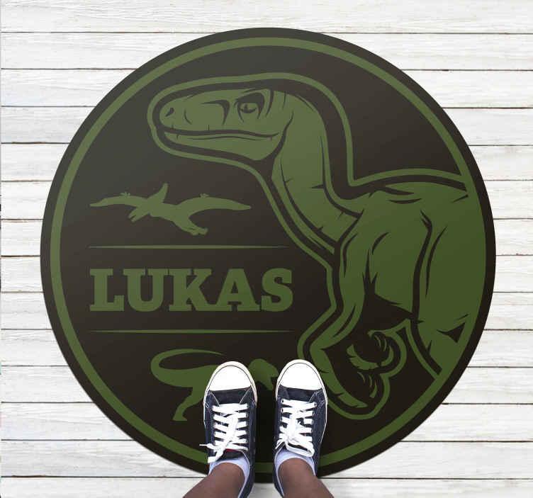 TenStickers. Raptor de dinossauro com tapete de animal de texto. Tapete preto e verde do quarto com a imagem de um dinossauro e um nome personalizável para que seu filho se sinta identificado. Disponível em 50 cores.