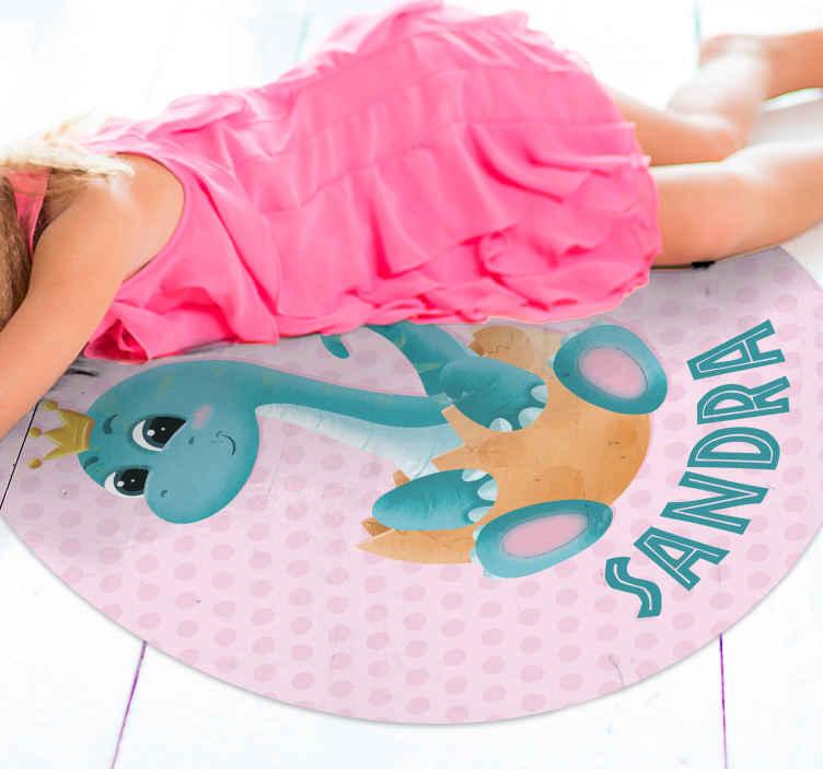 TenStickers. 恐龙与冠和名称乙烯基地毯. 让您的小女孩对这款带有皇冠乙烯基地毯的粉红色背景恐龙感到满意,您可以在上面添加她的名字。圆形!