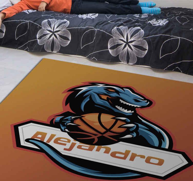 TenStickers. tapis vinyl personnalise Dinosaure de basket-ball personnalisé. Tapis en sticker de dinosaure qui présente une image d'un dinosaure tenant un ballon de basket avec un nom personnalisé en dessous. Haute qualité.