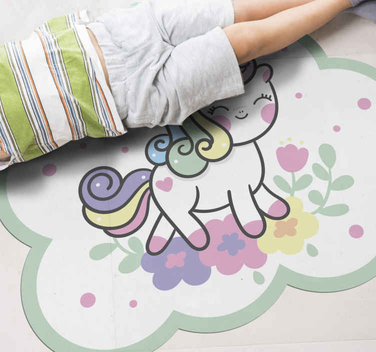 TenStickers. Unicorn smiling running in field kids vinyl carpet. Soft pinky and green colour children floor mat with design of a cute little unicorn happily smiling and running. The carpet is original and durable.