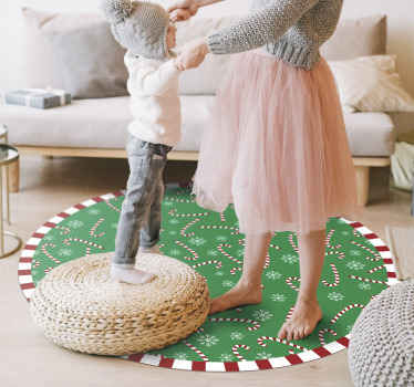 Green round tip vinyl rug designwith Christmas featured design. On the rug are candy sticks and snowflakes, round the tip is framed in candy pattern.