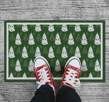 Tapis d'arbre de noël qui présente un sticker d'adorables arbres de noël tirant des visages très mignons! Le tapis est coloré en vert et blanc.