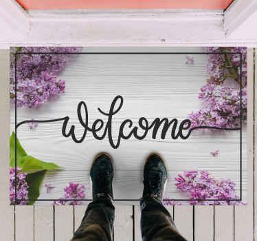"""这种木质乙烯基地毯设计在白色的木制背景上带有文字""""欢迎""""。由优质材料制成。"""